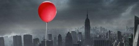 בלון אדום מעל עיר אפורה