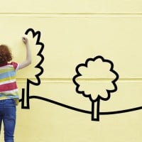 ילדה מציירת בית ועצים על קיר.