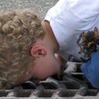ילד מסתכל בפתח ניקוז