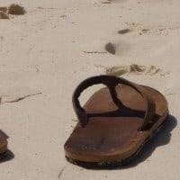 סנדלי אצבע על החוף עם עקבות