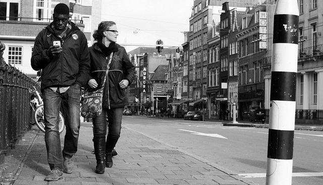 זוג הולך ברחוב שקוע בטלפון חכם