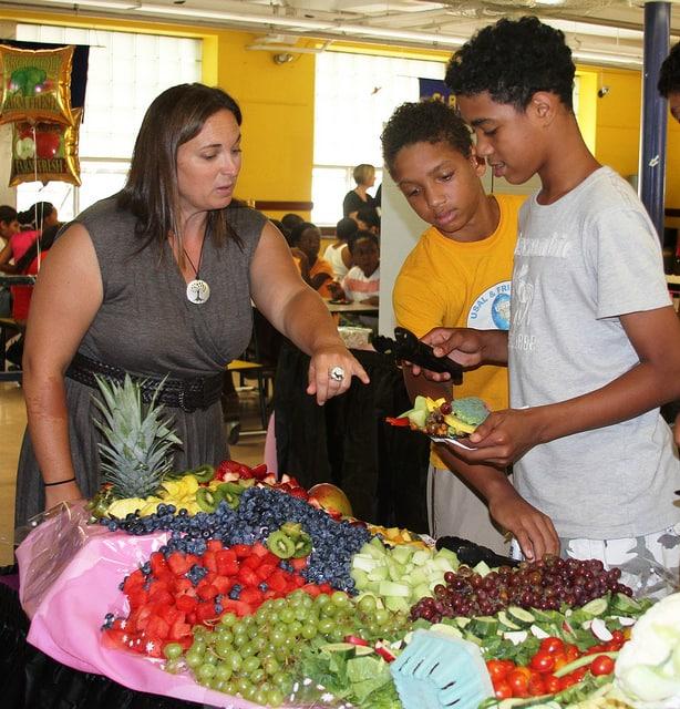 מתאמת של משרד החקלאות האמריקאי, פני וויבר, מעודדת תלמידי בית ספר לאכול פירות. צילום: משרד החקלאות האמריקאי