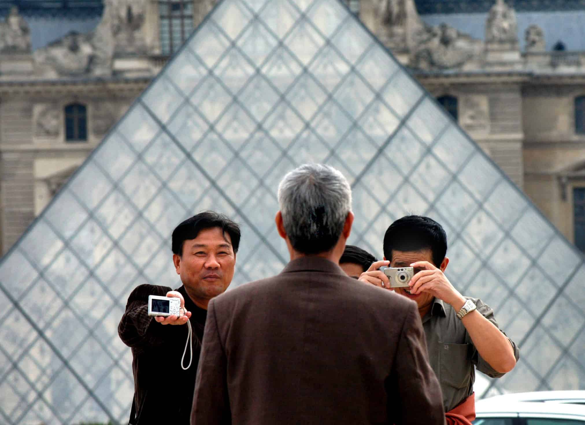 """תיירים סיניים בלובר. בשנה האחרונה יותר מ-83 מיליון תיירים סינים הוציאו יותר ממאה מיליון דולר בנסיעות לחו""""ל, מה שהופך אותם לאומה שמבזבזת הכי הרבה כסף על תיירות. צילום: """"בלומברג"""""""