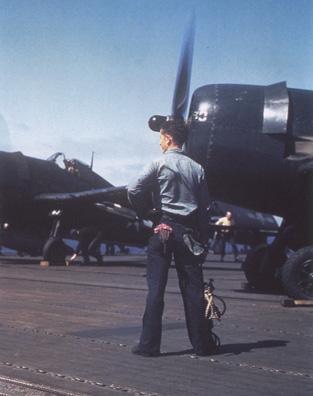 טייס אמריקאי עומד ליד מטוס מדגם F6F-5 Hellcats באוקינאווה, 1945.