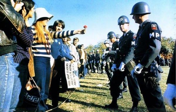 """מפגינה מושיטה פרח לשוטר בהפגנה בארה""""לֹ, אוקטובר 1969. צילום: צבא ארה""""ב"""