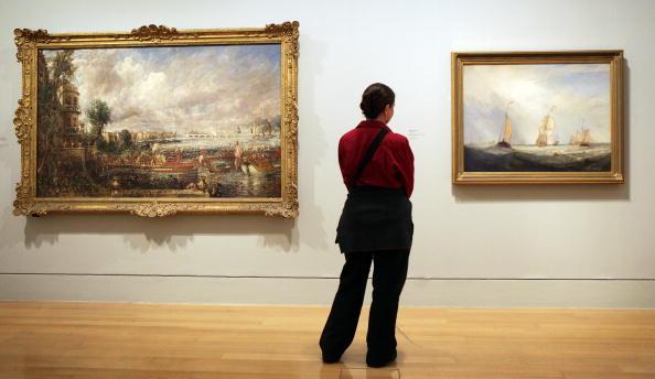 """מימין: ציורו של טרנר """"נוף ימי מאוטרכט"""" ליד הציור """"חנוכת גשר ווטרלו""""  מאת קונסטבל במוזיאון טייט בריטיין 2012. צילום: גטי אימג'ס"""