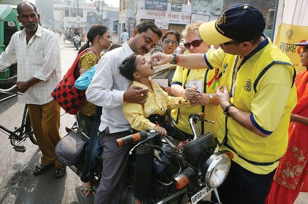 מתנדבים בריטים נותנים לילד חיסון נגד פוליו בהודו. צילום: RIBI Image Library
