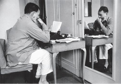 המינגווי יושב לצד מכונת כתיבה במלון דורצ׳סטר בלונדון, במהלך מלחמת העולם השנייה, קיץ 1944. צילום באדיבות פן הוצאה לאור
