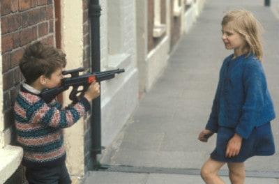 ילד מכוון נשק לילדה
