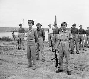 רוי פאראן, מימין, אוחז בתת מקלע MP40 הגרמני, במסדר של יחידת ה-SAS באוקטובר 1943, לאחר תפיסת נמל טרמולי במבצע מאחורי קווי האויב.