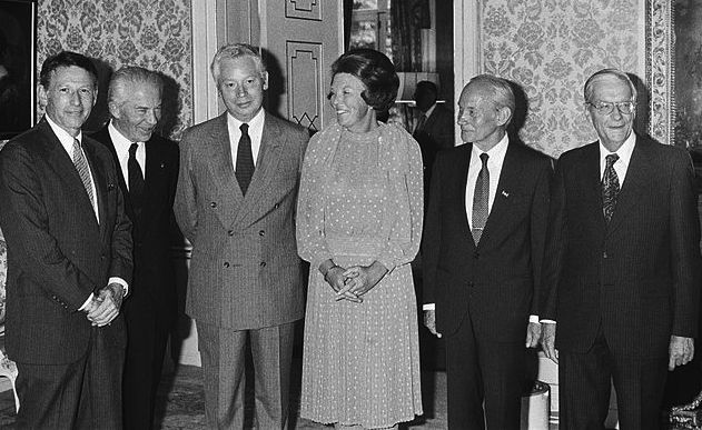 סטיבן ויינברג עומד משמאל לביאטריקס, מלכת הולנד, בטקס הענקת פרסי הנובל, 1979. באדיבות הארכיון הלאומי בהאג, הולנד.