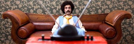 גבר יושב על ספה וצופה בטלוויזיה בשנות ה-70