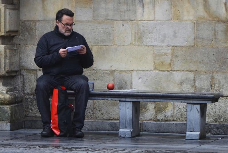 קורא על ספסל עם תפוח אדום