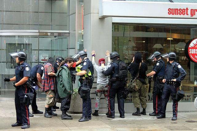 שוטרים בודקים מפגינים בוועידת G20 בטורונטו.