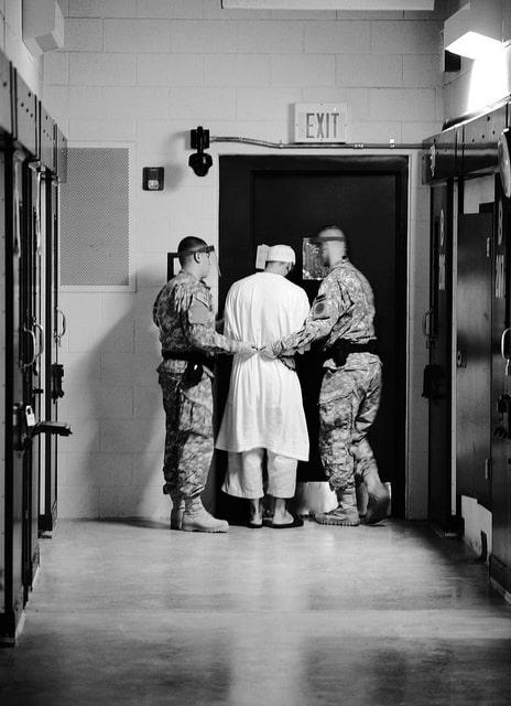 אסיר וסוהרים באחד ממחנות המעצר בגואנטנמו.