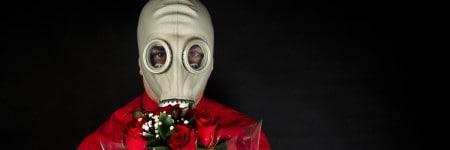 איש במסכת גז עם זר פרחים