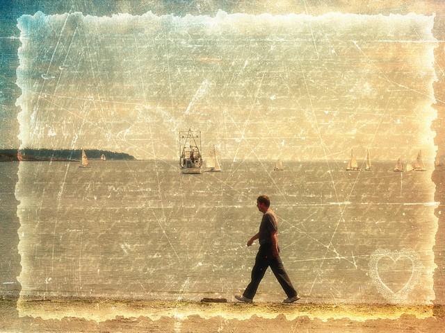 אדם הולך לאורך חוף עם סירות מפרש