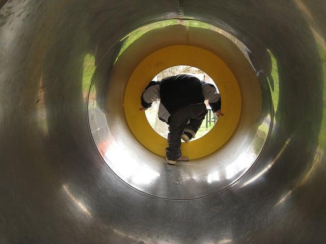 ילד בצינור בגן משחקים