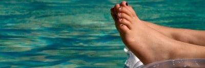 רגלי ילד על מזרן מתנפח בבריכה