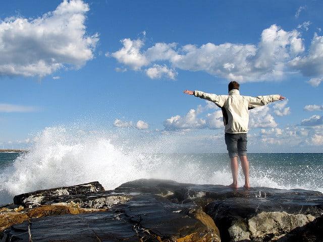 אדם פורש ידיים על צוק מול הים