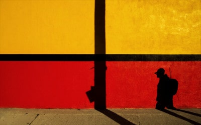 קיר צבעוני וצללית של אדם הולך