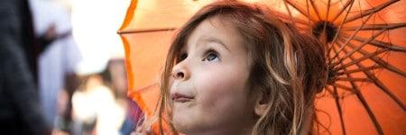 ילדה סקרנית מתחת לשמשייה כתומה