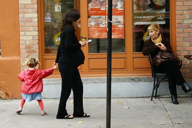 אישה בהיריון הולכת ברחוב עם ילדה קטנה