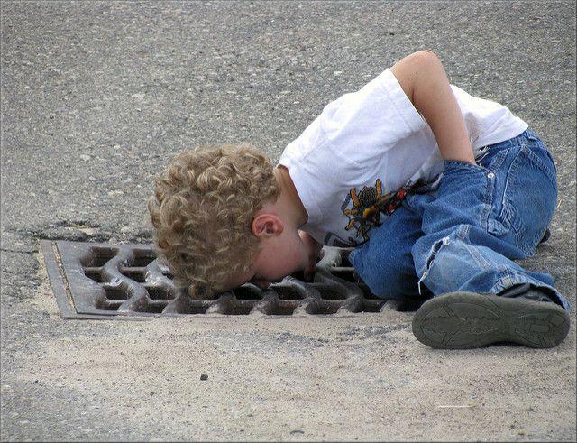 ילד מסתכל בפתח ניקוז ברחוב