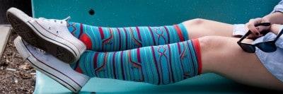 צעירה על ספסל, גרביים צבעוניות ונעלי התעמלות
