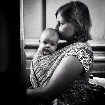 אישה ותינוק במנשא על הגוף
