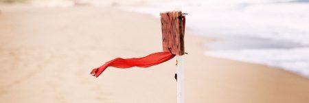 רוח, בד אדום, שלט עץ, שפת הים